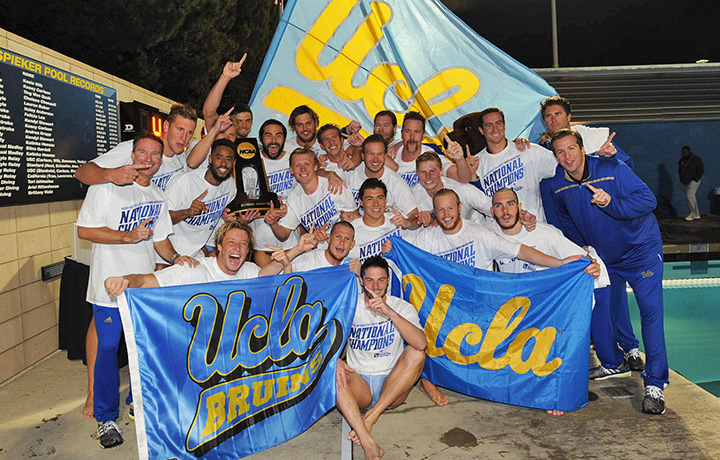 "male students hold UCLA flags and an NCAA trophy; most wear white t-shirts printed with the words ""National Champions"""