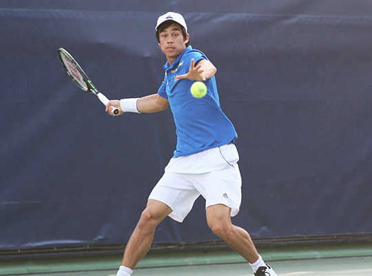 tennis player in blue polo shirt focuses on approaching ball