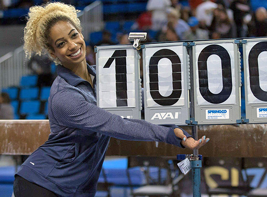 "gymnast in warmups poses with a ""10"" on the score flasher"