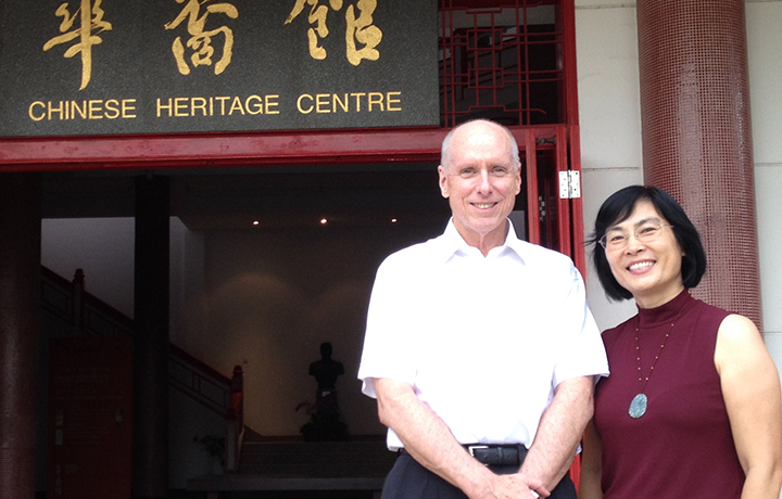 "Man and woman stand in front of sign with Chinese characters and English words ""Chinese Heritage Centre"""