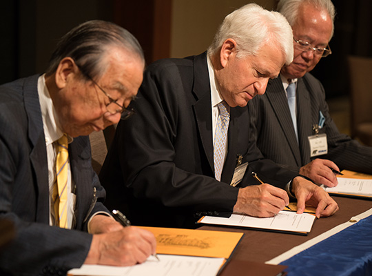 three men sit at a desk and sign documents
