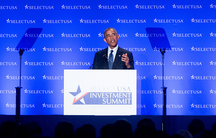 "the president stands in front of a screen with repeated ""SelectUSA"" logos; the podium sign shows a stylized red, white and blue star and the words ""SelectUSA Investment Summit"""