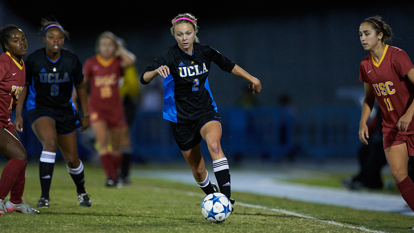 action shot of female soccer players in UCLA and USC uniforms