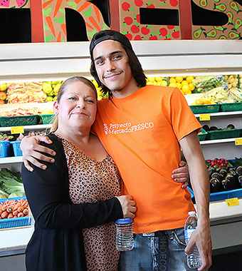 "Woman hugs young man in orange t-shirt printed with ""Proyecto MercadoFRESCO""; fresh produce displayed behind people"