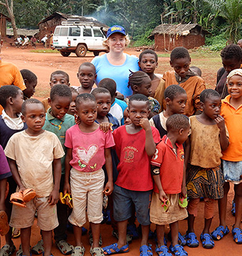 A group of children wearing ragged clothing, posing near a women wearing a blue cap and light blue t-shirt