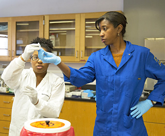 female student in white lab coat takes vial from female professor in blue lab coat